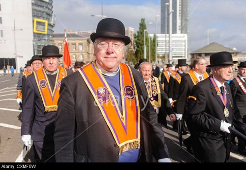 CXMF0W Chaplain Mervyn Gibson with a number of orangemen wearing 'Orange sash' and bowler hats during an Orange Order parade